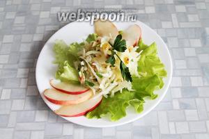 Разложить салат порционно на салатных листьях, украсить зеленью и дольками яблок.
