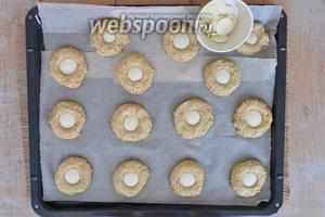 В середину каждого печенья поместить 1 медальон белой шоколадной глазури и прижать пальцем. Поставить выпекаться.