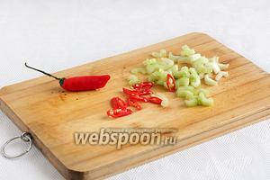 Измельчить 1/2 острого перца, стебель сельдерея нарезать кусочками.