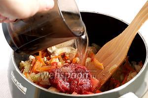 Добавить в сотейник томатную пасту или свежие помидоры, 2 щепотки сахара, чтобы нейтрализовать кислоту. Залить всё стаканом кипятка и варить примерно 10 минут.