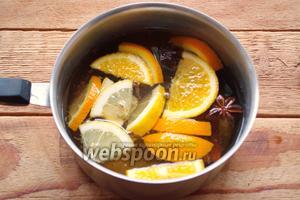 Снимите с огня. Нарежьте апельсин, лимон на небольшие кусочки. Добавьте в горячий напиток свежие фрукты. Слегка их подавите. Дайте настояться 15 минут.