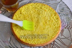 Приготовить ликёрную пропитку. Поставить нагреваться воду в небольшой кастрюльке, добавить сахар и ликёр (желательно, апельсиновый, типа Cointreau). Как следует перемешать до полного растворения сахара (не перегрейте!), снять с огня и дать остыть. Начинаем сборку торта. На блюдо положить первый корж, смочить его обильно пропиткой.