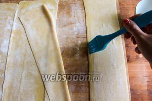 Смажьте края полосок теста холодной водой, чтобы полосы лучше склеились между собой.