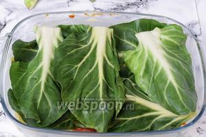 На томатный соус выкладываем зелёные листья мангольда. Так же равномерно делим по количеству листьев на слой.