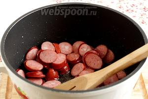 В казане обжарить колбаски на растительном масле.
