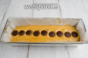 Форму для выпечки кекса застелить пергаментом. Влить 1/2 теста. Разложить по центру конфеты.