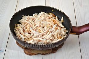 Добавьте в обжаренный лук с чесноком 1 столовую ложку кетчупа. Тщательно перемешайте, не снимая с огня. Положите в сковороду 1/3 куриного мяса и вновь перемешайте.
