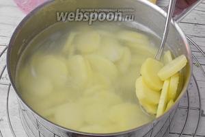 В закипевшую солёную воду закидываем очищенный и нарезанный пластинками 4-5 мм картофель. Не накрывая крышкой, проварим 3 минуты.