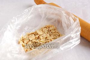 Кукурузные чипсы измльчить с помощью скалки. Для этого нужно положить их в пакет и прокатать скалкой.