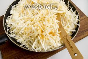 Добавьте нашинкованную капусту к луку, обжарьте всё вместе минут 5-7, периодически помешивая. Добавьте пряности, щепотку соли, перемешайте. И под крышкой томите на слабом огне до полной мягкости капусты.