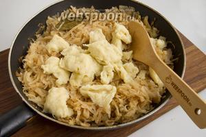 По 0,5 чайной ложки выкладывайте тесто в кипящую подсоленную 1 щепоткой соли воду, варите около 5 минут. Готовые галушки выкладывайте в готовую тушёную капусту. Перемешайте.