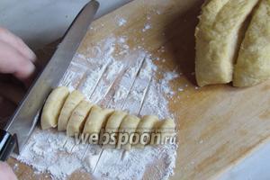 Сделать из них тонкие колбаски и, присыпав мукой, разрезать на мелкие кусочки, затем припорошить в муке.
