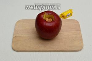 В углубление в яблоке вложить по 2 конфеты, кожицу аккуратно проколоть в нескольких местах толстой иглой или зубочисткой, чтобы при запекании она не лопнула и яблоко сохранило бы свою форму.