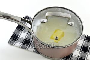 Снять с огня. Добавить сливочное масло. Накрыть крышкой и оставить кашу под крышкой ещё на 5 минут.