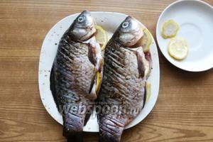 В брюшко каждой рыбки положим несколько кружков лимона.