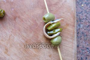 Прокалываем свободный конец анчоуса и закрепляем всё оливкой.