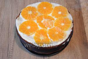Сверху кладём третий корж, повторяем процедуру. Теперь фруктовой прослойкой будет служить мандарин. Мандарин очистить от кожуры и белых плёночек, порезать тонкими кольцами. Выложить мандарин по кругу.