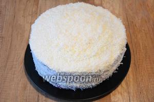 Смазать, оставшимся количеством крема, торт по бокам и сверху. Посыпать кокосовой стружкой бока и верх торта.