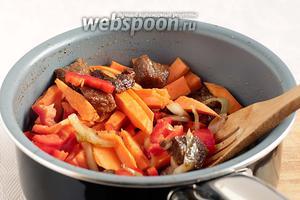 Добавить в сотейник морковь и сладкий перец. Обжаривать при помешивании до лёгкого изменения цвета.