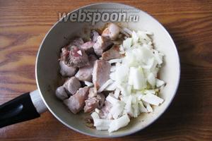 Репчатый лук очищаем, моем и режем кубиками или полукольцами. Добавляем к жареной свинине. Наливаем ещё подсолнечное масло и тушим свинину с луком 10-15 минут, периодически перемешивая.