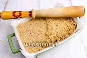 Подготовить форму. Застелить её пергаментной бумагой. Выложить в форму сладкую массу. Уплотнить с помощью валика или деревянной толкушки.