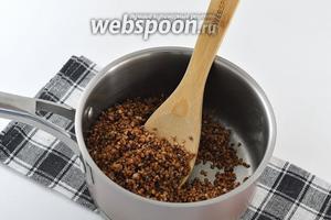 Всыпать гречку к маслу и перемешать таким образом, чтобы каждая крупинка обволоклась тонким слоем масла.