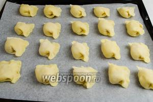 Выложить заготовки на пергамент. Поставить противень в горячую духовку. Запекать печенье 30 минут до румяности при температуре 180°C.