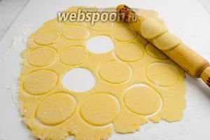 На хорошо подпылённую мукой (примерно 80 г.) поверхность стола выложить тесто. С помощью скалки раскатать тесто. Вырубкой или просто стаканом нарезать круги диаметром 6 см.