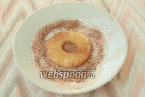 С ананасовых колец как раз стечёт жидкость, за всё это время, но можно их ещё слегка отжать, чтоб меньше капало в тарелку. Сахар перемешать с молотой корицей, обмакнуть в этой смеси кольцо ананаса с двух сторон.