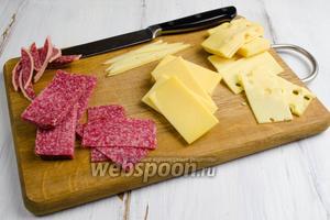 Готовить это блюдо, желательно, в перчатках. Сделать выкройку-прямоугольник из бумаги в клетку размером 6х3 см. Сложить в стопку сыры и колбасу. Приложить выкройку и острым ножом нарезать прямоугольники нужного размера. Сыр с гладкой поверхностью используем на верх косточки домино. Второй сорт сыра будет служить основой.