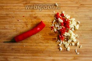 1/4 перчика чили очистите от семян и прожилок, а затем мелко порубите. Чеснок тоже мелко порубите ножом.