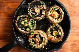 Прямо в форме перемешайте шампиньоны руками, чтобы они со всех сторон покрылись маслом с пряностями и щедро присыпьте грибы солью и свежемолотым чёрным перцем.