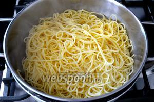 Одновременно в закипевшую подсоленную воду выложить спагетти и отварить до готовности. Откинуть пасту на дуршлаг, часть воды лучше сохранить, на случай, если понадобиться чуть разбавить томатный соус.