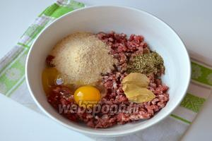 Приготовить фарш для тефтелек. В миску выложить говяжий фарш, панировочные сухари, яйцо, горчицу, мелко изрубленные «иголочки» розмарина и орегано.