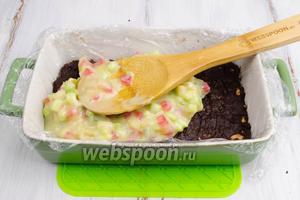 Форму с шоколадной массой вынуть из морозилки. Распределить второй слой бело-шоколадный с цукатами.