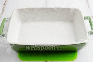 Форму сполоснуть водой. Так легче будет расстелить пищевую плёнку по дну и стенкам формы.