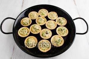Разложить улитки с сырной массой в тарталетки. Поставить в горячую духовку. Запекать в течение 5 минут при температуре 250°C.