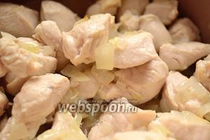 В казане или сотейнике с толстым дном разогреть растительное (подсолнечное рафинированное) масло и обжарить в нём сначала лук 1-2 минуты до прозрачности. Затем добавить к нему курицу. Обжаривать всё вместе буквально 3-4 минуты, иногда помешивая. Курица должна побелеть.