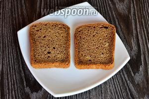 Укладываем 2 кусочка чёрного хлеба на тарелку.