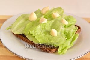 На зерновой хлебец положить листья айсберга. Рвём листья крупно, прямо руками. Сверху положить немного майонеза.