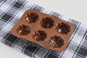 В небольшие формочки для конфет выложить по чайной ложке шоколада.