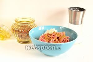 К фаршу добавить 1 столовую ложку риса, соль и специи по вкусу. Всё перемешать.