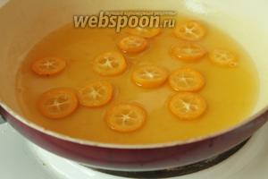 Выжать сок апельсина, перелить в миску, положить сахар и поставить на огонь, помешивая, чтобы сахар полностью растворился. Как только жидкость закипит, сразу положить в сироп дольки кумкватов. Проварить минут 5-7  и снять с огня.
