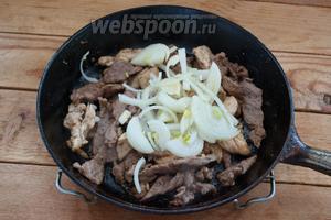 К обжаренному мясу добавьте репчатый лук. Потом добавляем шампиньоны. Жарим всё вместе до готовности.