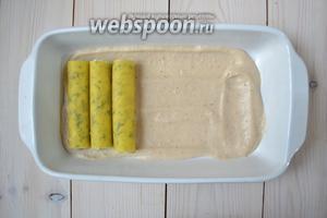 Выложите на дно формы несколько столовых ложек соуса, а на него — начинённые каннеллони.