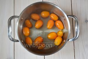 Наберите в кастрюлю немного воды и доведите её до кипения. В кипящую воду положите кумкваты и бланшируйте 1 минуту.