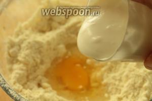В сметану добавить соду, перемешать. Сделать в масляно-мучной смеси углубление и вбить туда 1 яйцо и влить сметану.
