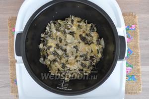 В чашу мультиварки налить немного масла и выложить 1/2 картофеля, равномерно распределяя по чаше. На картофель выложить ровным слоем весь папоротник.