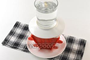 Концы марли завернуть наверх. Сверху выложить блюдце, а на него небольшой груз (стакан с водой). Отправить в холодильник на 12 часов. Время от времени сливать жидкость, вытекающую на нижнее блюдце.
