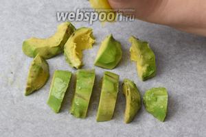 Нарезаем авокадо толстыми кусками. Перекладываем на пекарскую бумагу на противне. Выдавливаем сок из лимона, около 1 ст. л., на авокадо.